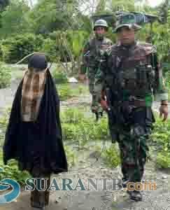 ISTERI SANTOSO SERAHKAN DIRI - Isteri Santoso, Jumiatun alias Umi Delima (tengah) diamankan anggota Satgas Operasi Tinombala setelah menyerahkan diri di Poso, Sulawesi Tengah, Sabtu (23/7/2016). Jumiatun yang masuk salah seorang dalam DPO kelompok Santoso menyerahkan diri ke Satgas Operasi Tinombala Sabtu (23/ 7) pagi setelah kelelahan dan kelaparan 6 hari tidak makan karena melarikan diri dari sergapan pasukan TNIPolri yang memburunya sejak kontak senjata pada Senin (18/7/2016) yang menewaskan Santoso dan Mukhtar (Bali Post/ant)